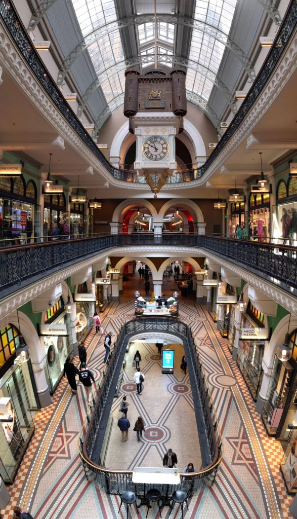 Inside of the Queen Victoria Building as it's a multi-level shopping center and has a clock tower coming from the ceiling.