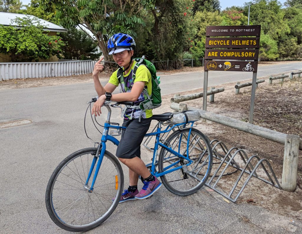 Justin Huynh, Life Of Doing, is on a bicycle and wears a helmet. At Pedal and Flipper Bicycle Rental on Rottnest Island.