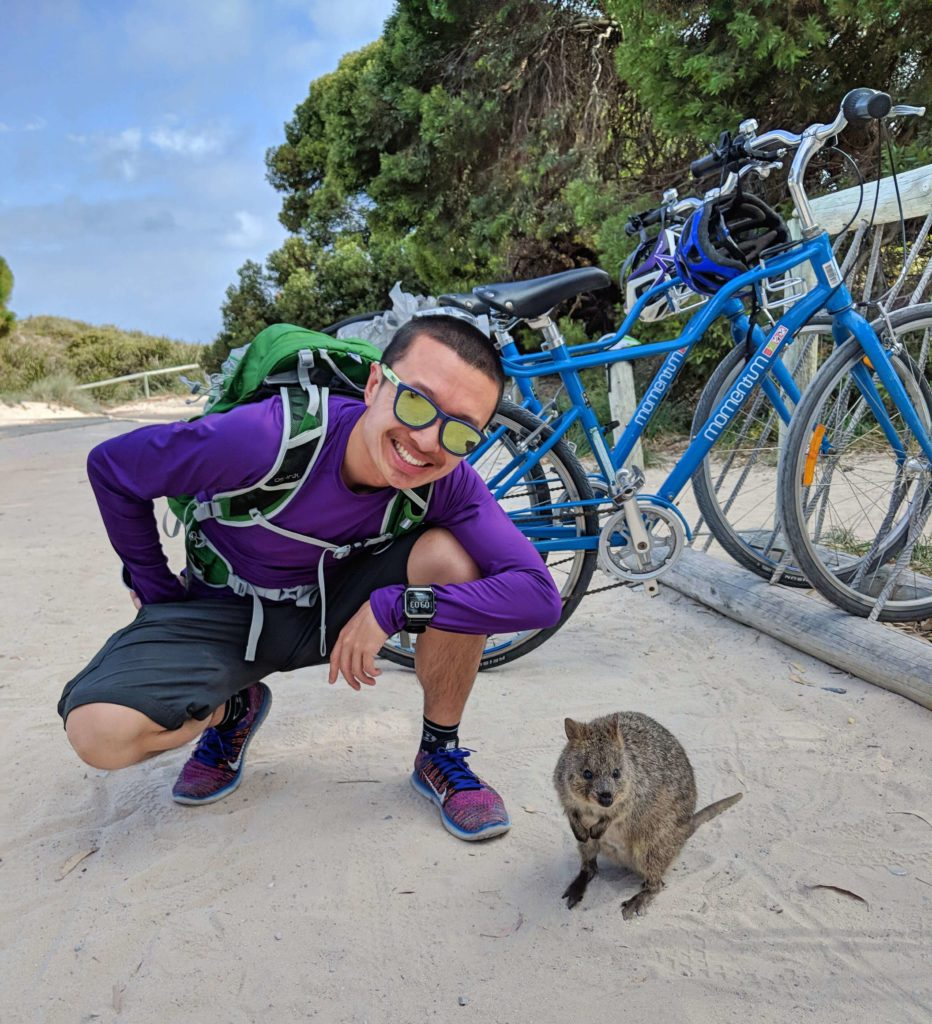 Justin Huynh, Life Of Doing, stands next to a quokka at Rottnest Island, Australia
