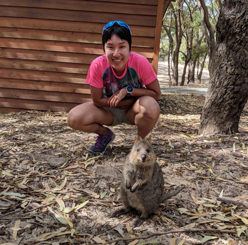 Jackie Szeto, Life Of Doing, poses next to a quokka on Rottnest Island, Australia