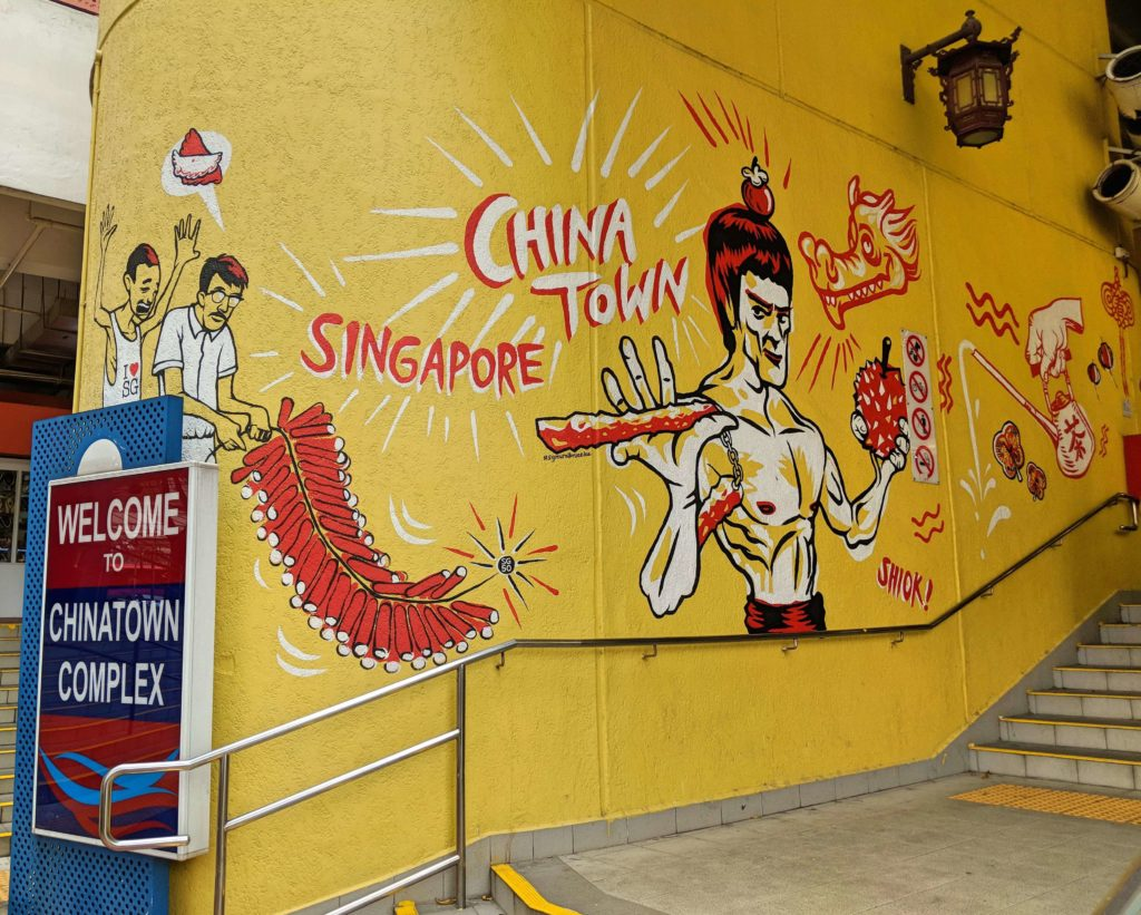 Chinatown Complex Sign with a drawing of Bruce Lee on the wall.