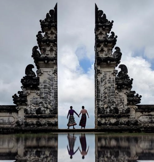 Justin Huynh and Jackie Szeto, Life Of Doing, hold hands at Lempuyang Temple's Gateway to Heaven, a perfect day trip from Ubud.