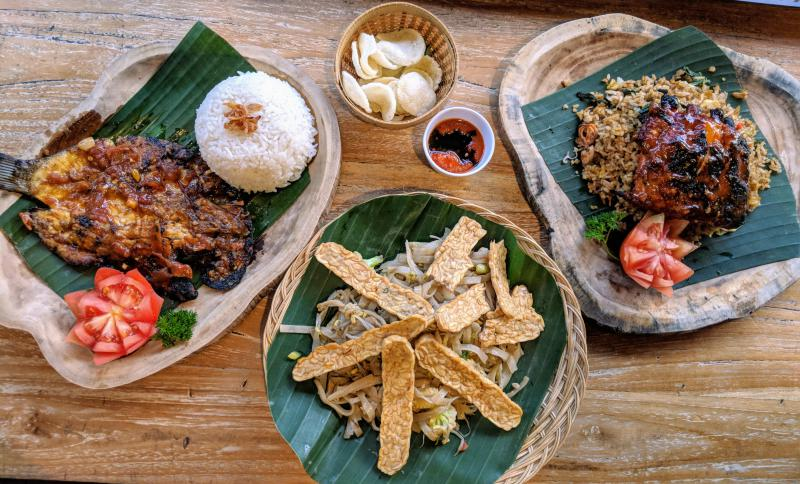 A meal Warung Pandok Madu in Ubud, Bali, Indonesia which has grilled fish, pork ribs and rice, and tempeh.