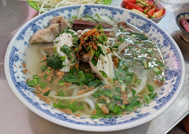 Hot bowl of bánh canh bột lọc which has banh canh noodles, fish cakes, pork bone, chicken, and fish cakes. It's a good place for breakfast in Phu Quoc, Vietnam.