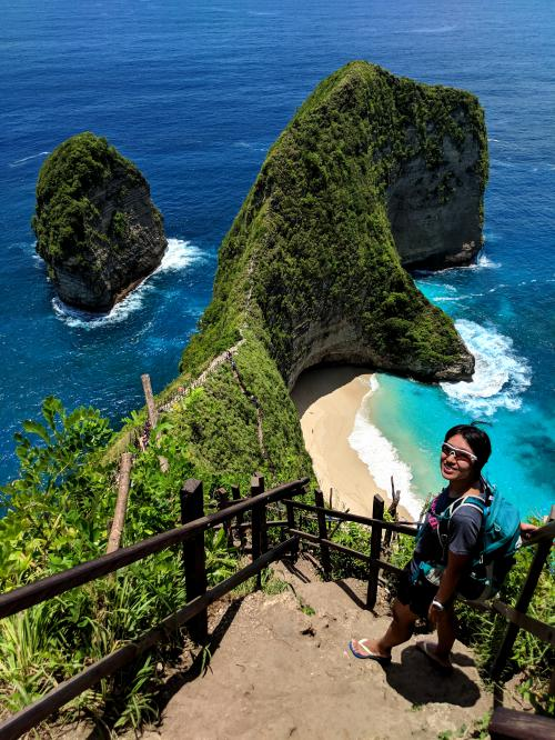 Jackie Szeto, from Life Of Doing, stands along the cliff side admiring the ocean and beach landscape of Kelingking Beach in Nusa Penida, off of Bali, Indonesia