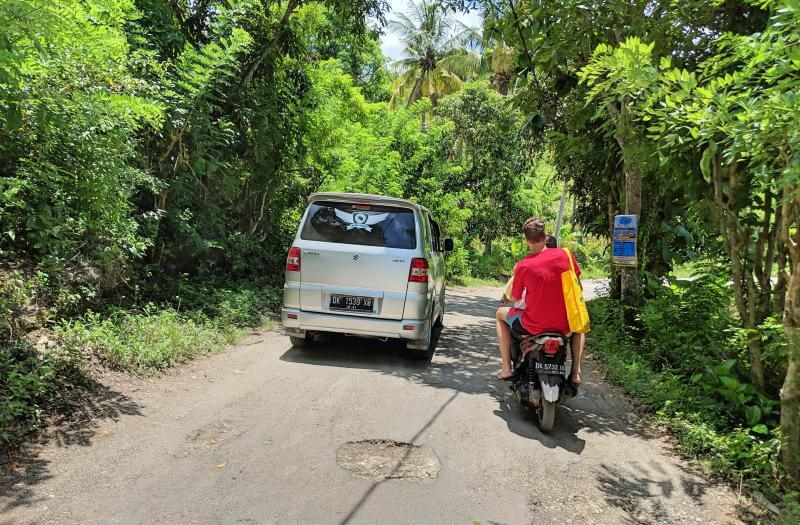 Cars and motorbikes must share the roads on Nusa Penida. The roads aren't wide and filled with deep potholes.