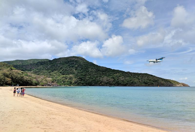 A group of women watch the plane fly over Dam Trau Beach in Con Dao Islands, Vietnam