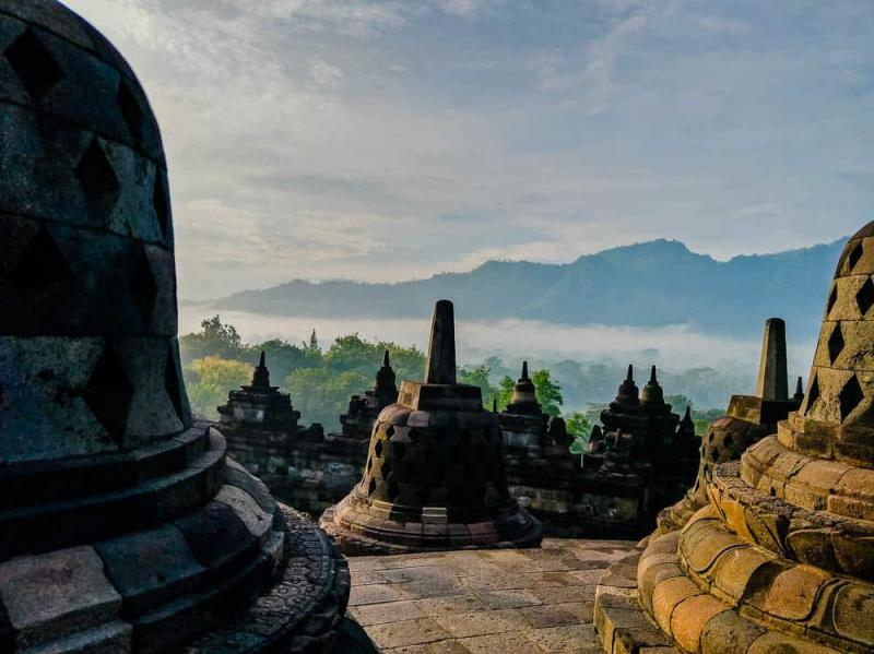 Borobudur Temple is one of the UNESCO World Heritage Sites to visit in Indonesia. Stop by here to see large Buddhist temple complex with the bell-shaped temples.