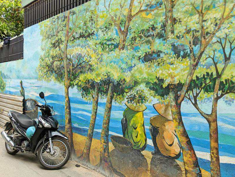 Danang has a vibrant street art scene. In your Danang itinerary, check out the Danang Fresco Village alleyway which highlights the Vietnamese daily lifestyle and culture. This artwork has two men relaxing along the coastline.