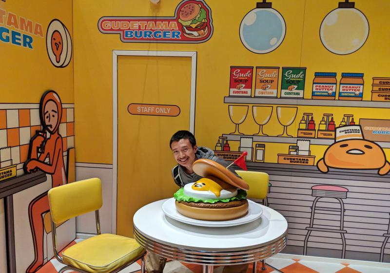 Sanrio Puroland's Gudetama Land has a Gudetama (lazy egg) theme where you can take photos and pose with Gudetama inspired artwork and statue. In this photo, Justin poses with Gudetama in a hamburger.