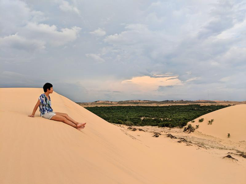 Jackie is sitting on top of the Mui Ne's white sand dunes.
