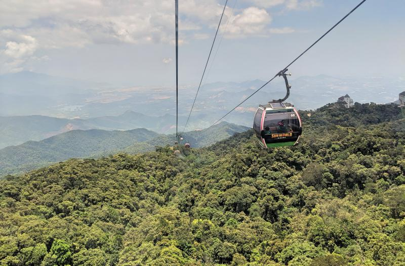 We're riding one of the longest cable car lines at Ba Na Hills in Danang, Vietnam. The views of the greenery and trees are beautiful from the cable car.