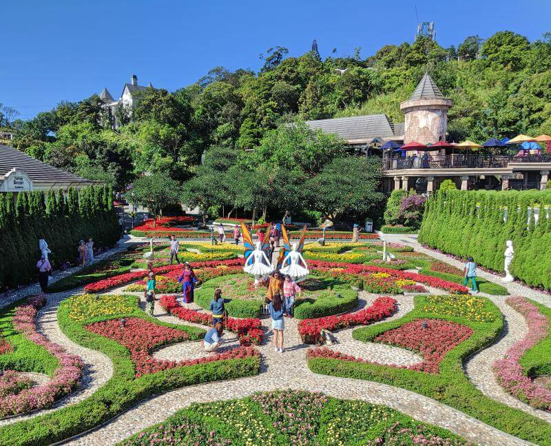 Sun World Ba Na Hills has picturesque gardens to explore and take photos. This central garden has yellow, red, and pink flowers in a maze-like architecture.