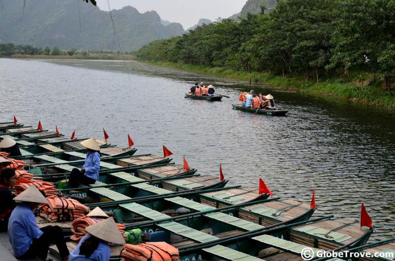 Local rowers wait in their boat until it has a full capacity of four riders. There are two boats in the distance as they head to the karst landscapes in Trang An, Vietnam.