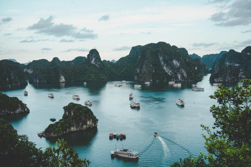 Panoramic view of Halong Bay, one of the UNESCO World Heritage sites in Vietnam. The junk boats navigates through the calm bay waters as visitors observe the limestone karsts.