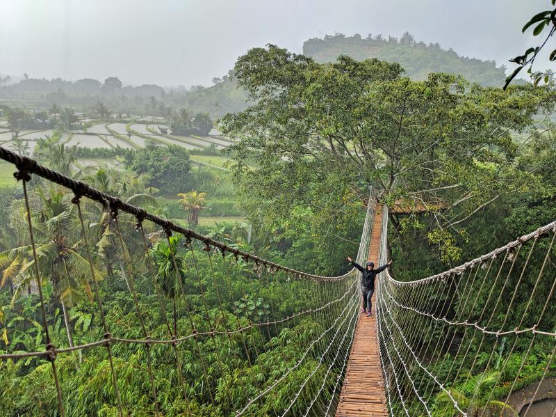 Jackie Szeto, Life Of Doing, stands on a long suspension bridge at Bukit Lemped. The bridge overlooks a rice field and a river underneath.