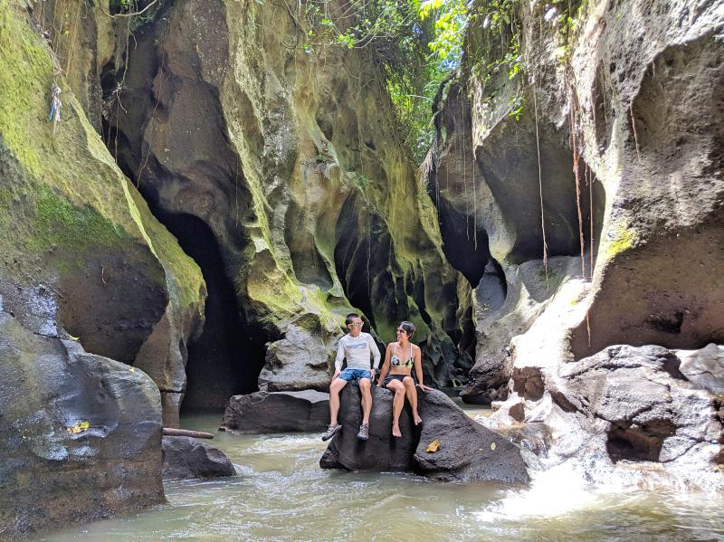 Justin Huynh and Jackie Szeto, Life Of Doing, enjoy their time sitting on a large rock at Hidden Canyon in Bali.