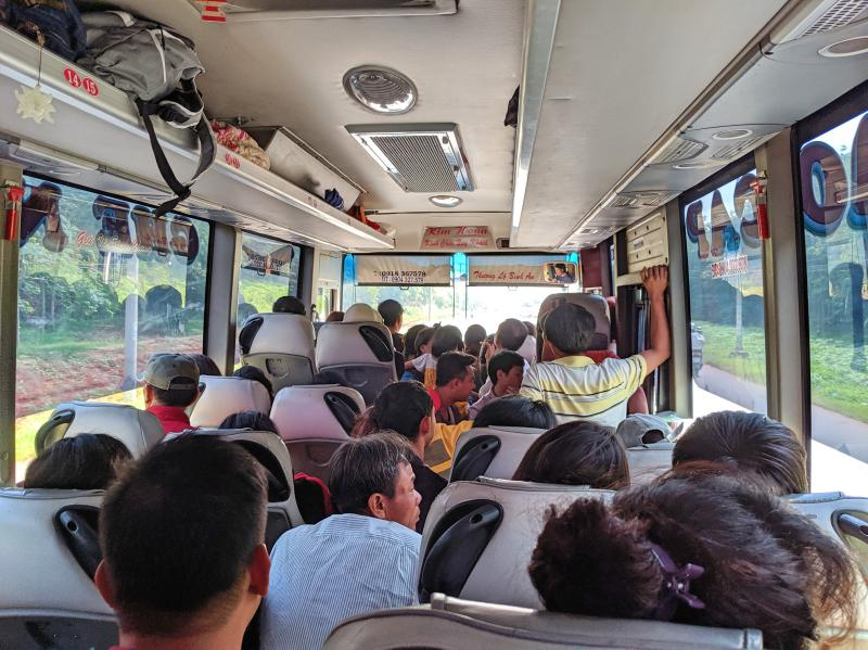 Local bus from Ho Chi Minh City to Cat Tien National Park that is overfilled with people. The aisle is also used as seats.