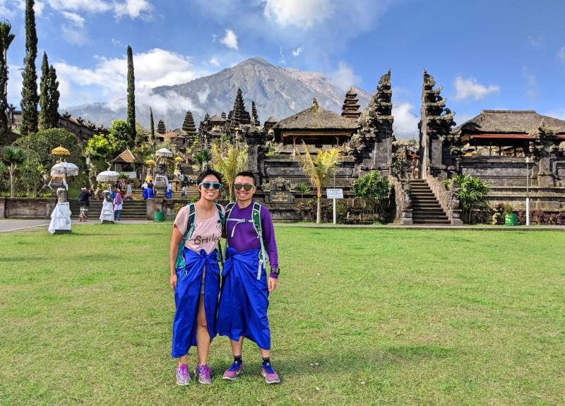 Jackie Szeto and Justin Huynh, Life Of Doing, stand in front of Besakih Temple with Mount Agung in the background