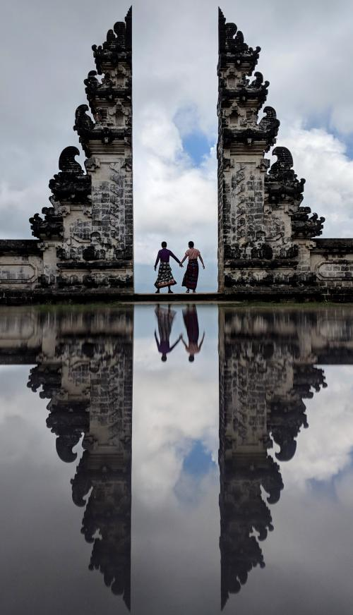 Justin Huynh and Jackie Szeto, Life Of Doing, hold hands at the famous Pura Lempuyang's Gateway to Heaven with a reflection at the bottom.
