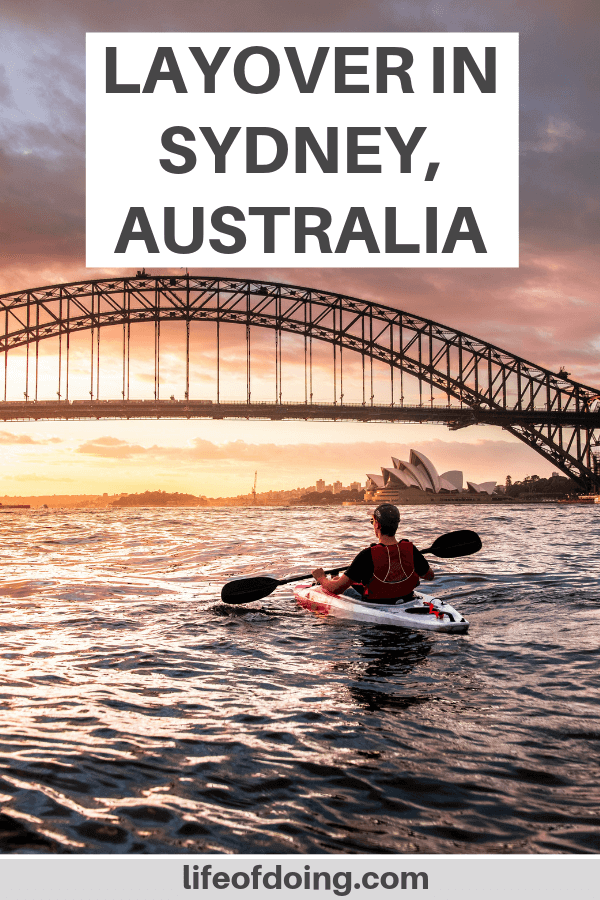 We're sharing what to do during a layover in Sydney, Australia. In this photo, there is a man kayaking in the sunset and the view of the Harbour Bridge.