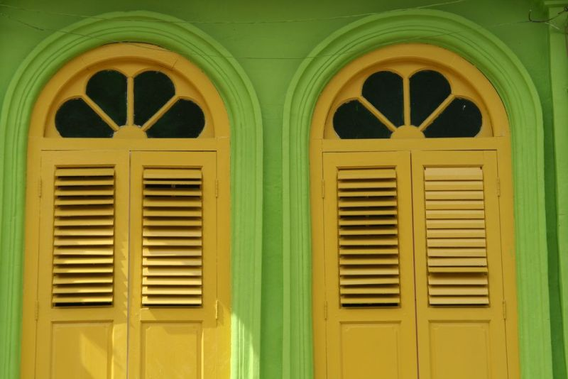 Lime green house with yellow window covers along Arab Street in Singapore.
