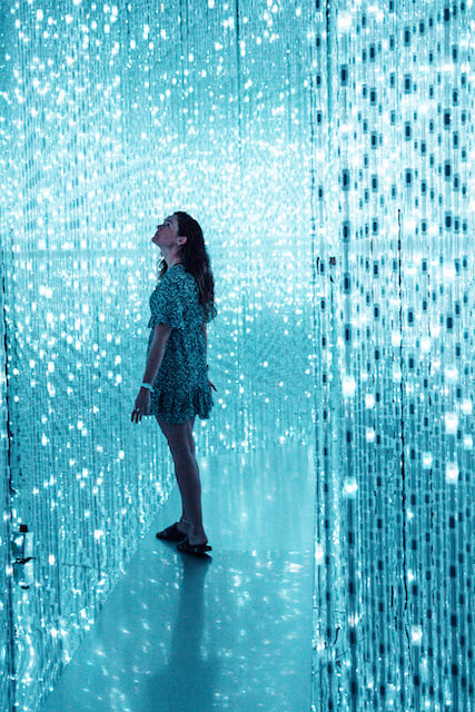 A woman walks through the blue lighted crystal displays at Singapore's ArtScience Museum featuring teamLab's Future World.