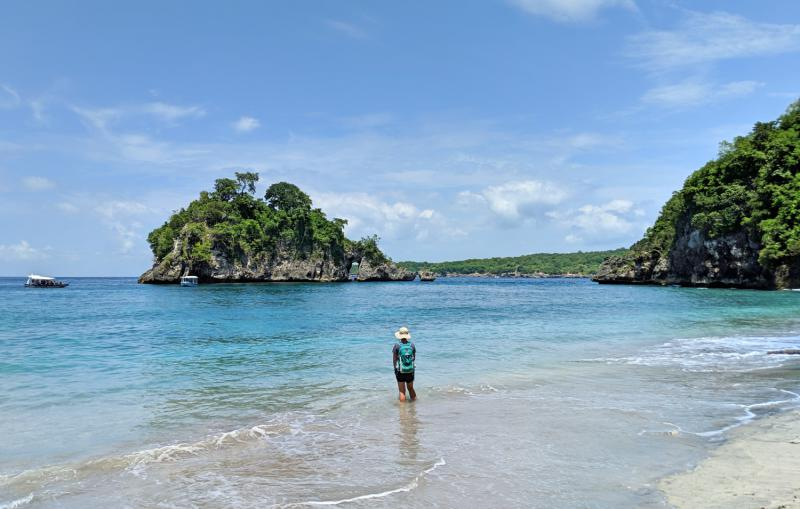 Jackie Szeto, Life Of Doing, stands in the blue waters off of the Crystal Bay Beach in Nusa Penida, Indonesia.