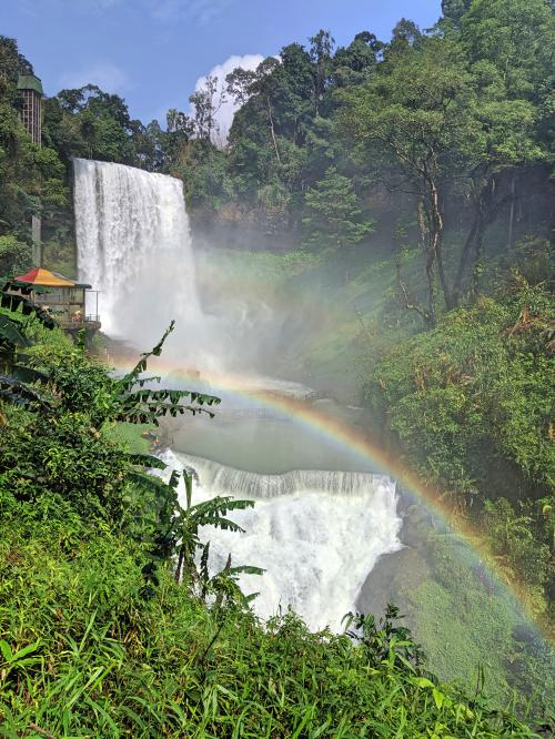 View of the Dambri Waterfall with a rainbow