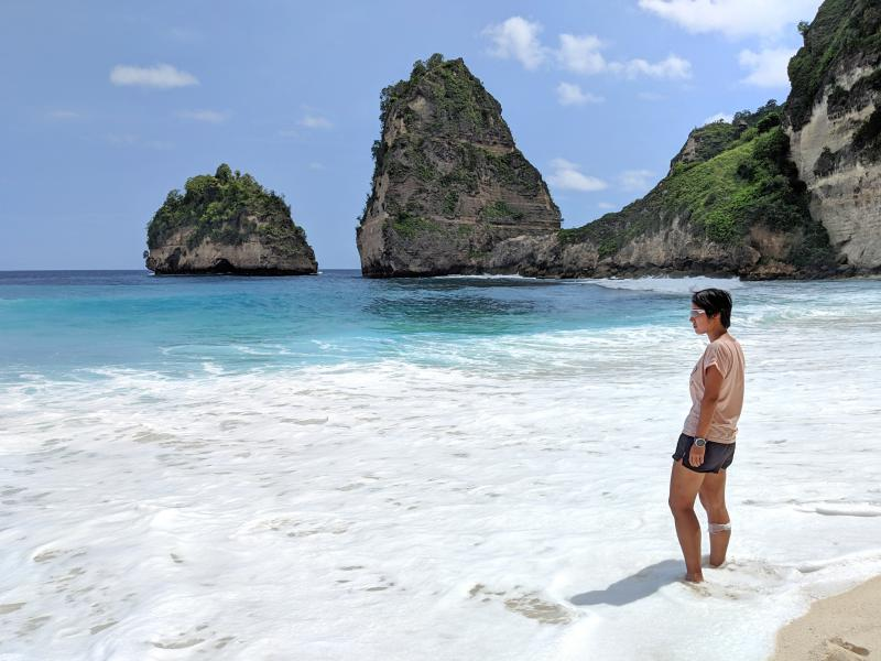 Jackie soaks her feet in the waters of the Nusa Penida's Diamond Beach