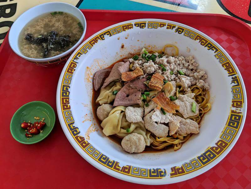 Bowl of bak chor mee which has meat balls, pork, dumplings, ground pork, and noodles with soup on the side. This is at Singapore's Hill Street Tai Hwa Pork Noodle Shop.