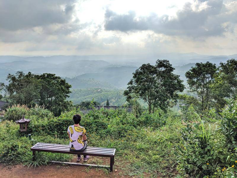 Jackie Szeto, Life Of Doing, sitting on a bench while overlooking the green mountainside at Linh Quy Phap An Pagoda in Bao Loc, Vietnam.