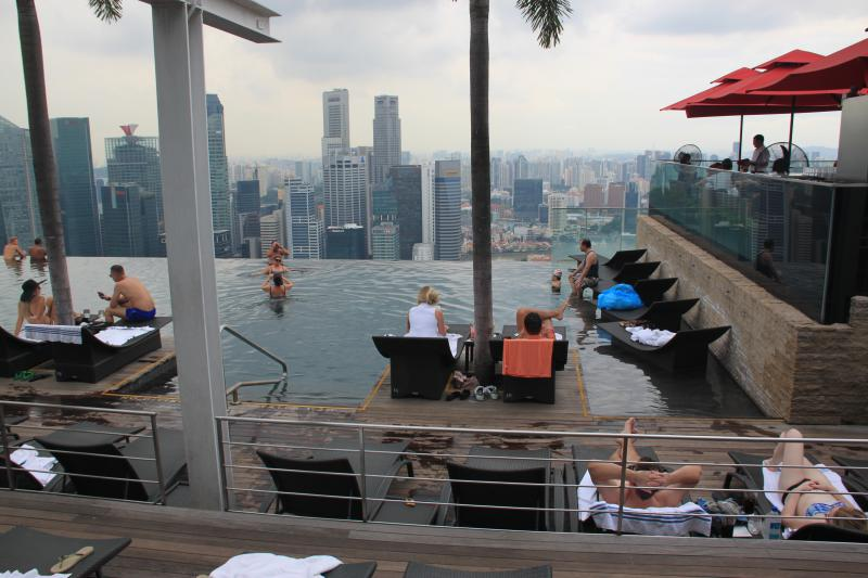 People relaxing and swimming at the infinity pool at the Singapore's Marina Bay Sands rooftop.