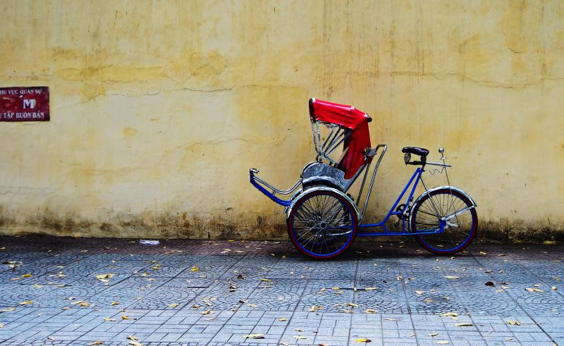 Blue cyclo with a red cover for the guests parked on the sidewalk of Ho Chi Minh City, Vietnam