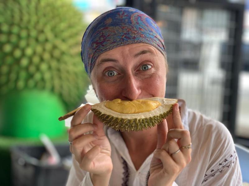 Woman eating a piece of durian in Petaling Jaya, Malaysia