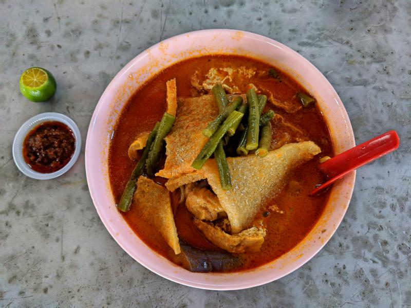 A bowl of curry laksa with tofu, eggplant, green beans, and a side of chili sauce and lime.