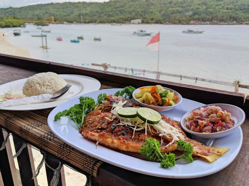 Enjoying fish and rice with a view of the water from Seaweed Seafood and Grill, a top restaurant in Nusa Lembongan.