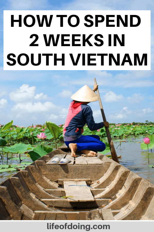 2 weeks in South Vietnam itinerary. Photo of a Vietnamese woman wearing a conical hat and rowing a sampan between the pink lotus
