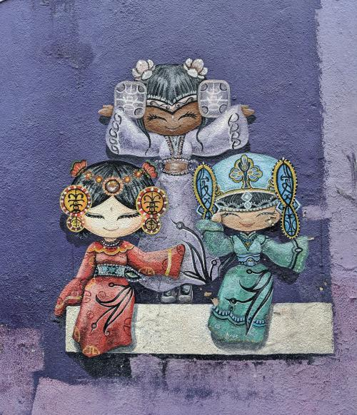 Penang street art in George Town that has three women in their traditional outfits - Chinese, Malaysian, and Indian