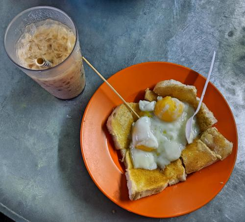 Iced tea with a plate of buttered toast with egg at Toh Soon Cafe in Penang