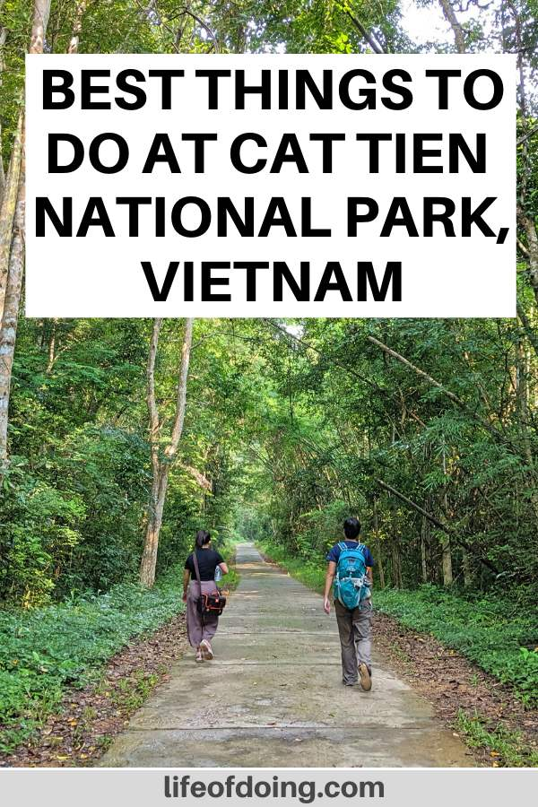 One of the top things to do at Cat Tien National Park in Vietnam is to walk around the forest area and explore nature. Two women are walking on the sidewalk going towards the hiking trail.