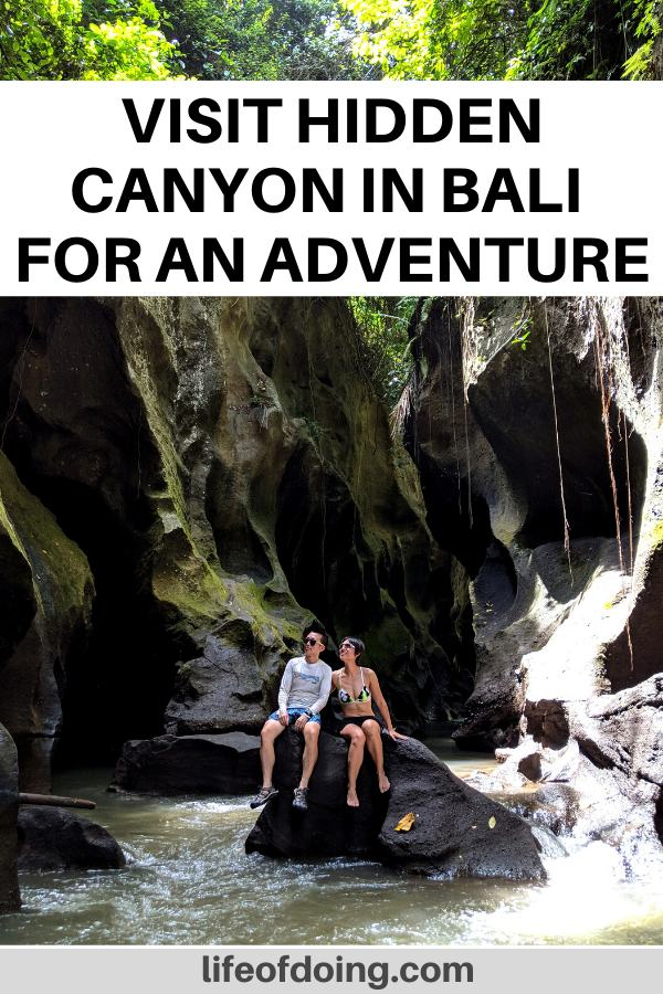 Jackie and Justin go canyoning at Hidden Canyon in Bali, Indonesia. They are sitting on a rock and looking up in the sky in the canyon.