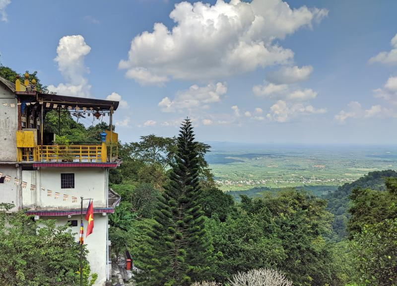 We're at a viewpoint from the Buu Quang Pagoda on Chua Chan Mountain. It's a lovely view with the greenery and trees.