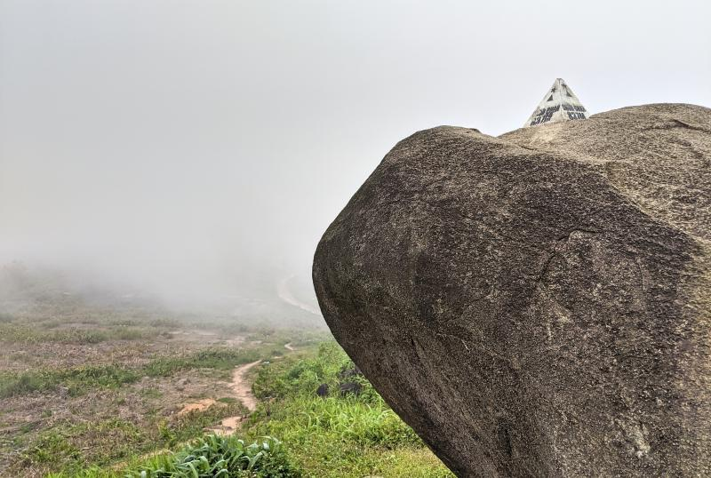 Summit of Chua Chan Mountain with the landmark marker on the giant boulder with the fog rolling in.