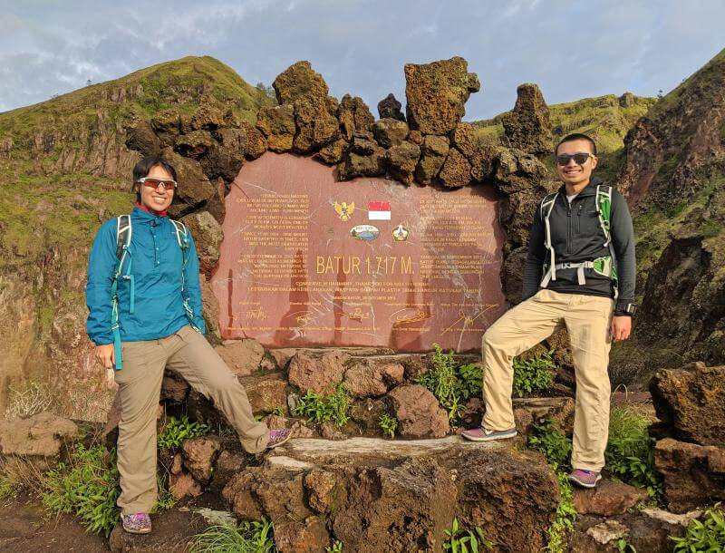 Jackie and Justin reach the Mount Batur summit sign that says 1717 meters. Check out our post on what to expect for trekking Mount Batur in Bali