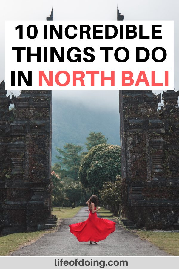 Woman in red dress twirls in front of the Handara Gate in North Bali. Check out our post on the top things to do in North Bali, Indonesia.