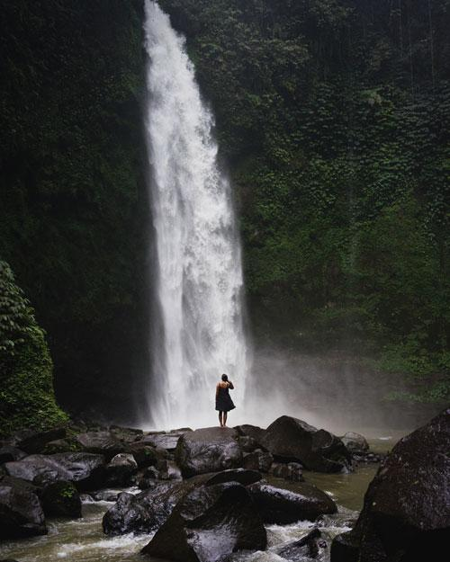 A woman wearing a dress poses in front of the Nungnung Waterfall in Bali, Indonesia. Check out this post to learn more about the best waterfalls in Bali.