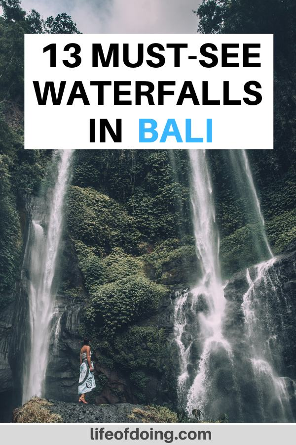 A woman in a dress standing in front of the Sekumpul Waterfall, one of the best waterfalls in Bali to visit.