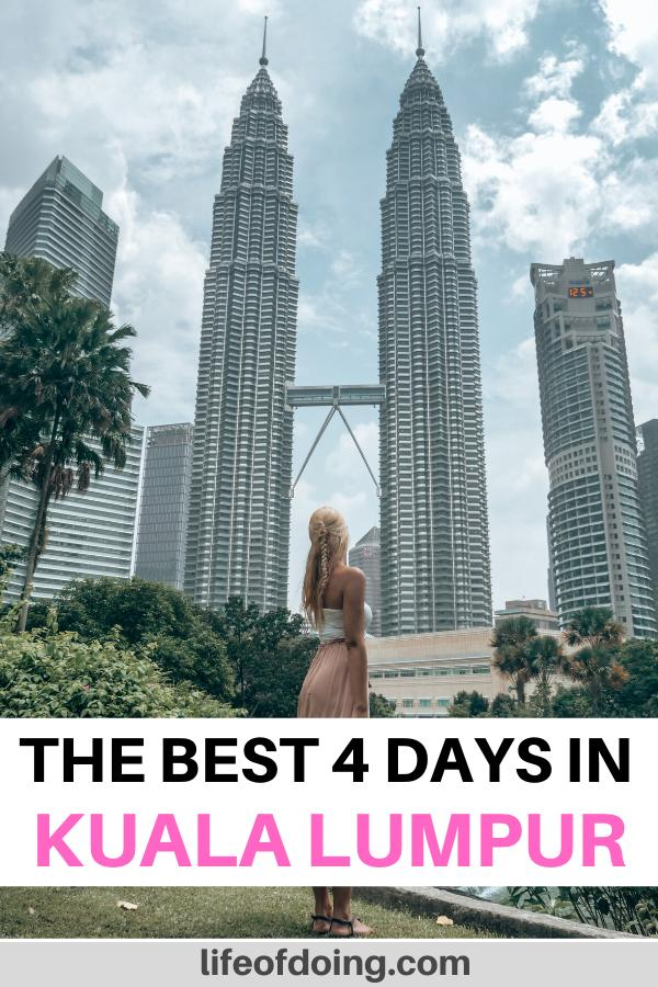 A woman in a dress looks at Kuala Lumpur's Petronas Twin Towers, which is one of the places to visit when you have 4 days in Kuala Lumpur, Malaysia.