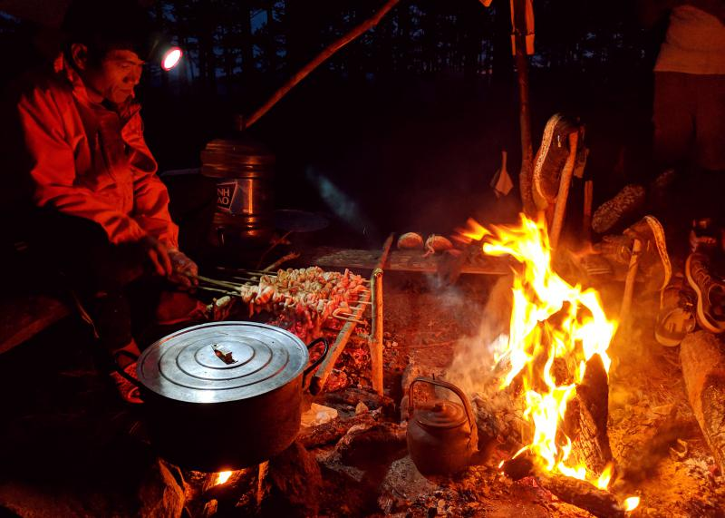 A man, chef from To Ong Adventure, cooks dinner next to a campsite fire for the hikers on the Bidoup trek. Dinner consists of pork on skewers and noodle soup.